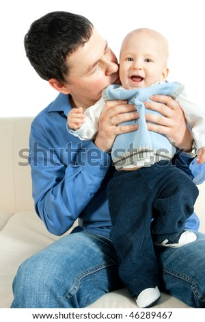happy family: father and baby sitting on the sofa and smiling - stock photo