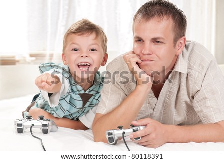 Happy family - father and child playing a video game - stock photo