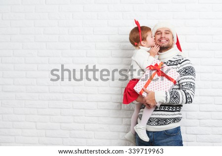 Happy family father and child with a gift in a Christmas kiss from a blank brick wall - stock photo