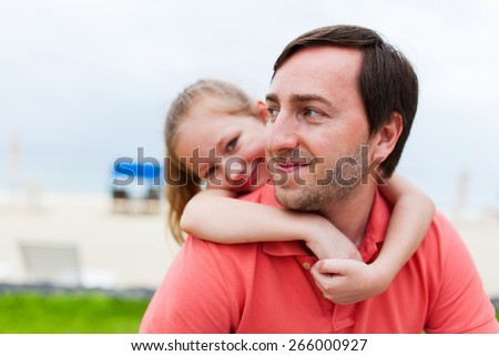 Happy family father and his adorable little daughter at beach on summer vacation - stock photo