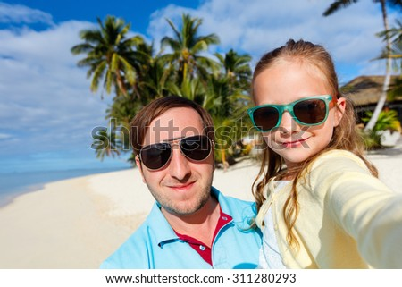Happy family father and his adorable little daughter at beach taking selfie - stock photo