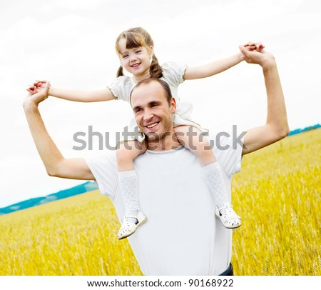happy family;  father and his daughter at the wheat field on a sunny day (focus on the  man) - stock photo