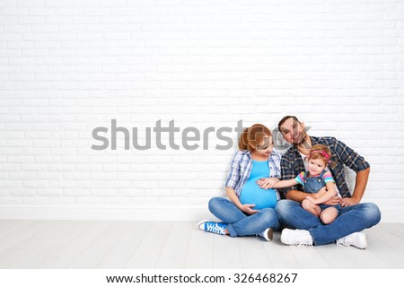 Happy family father and pregnant mother and child daughter near a blank brick wall in the room - stock photo