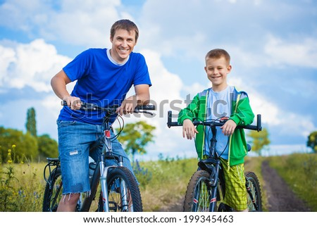 Happy family. Father and son riding  in the summer park - stock photo