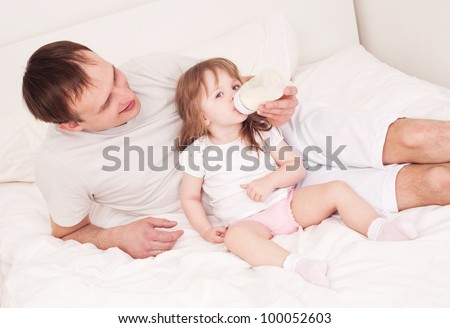 happy family;  father feeding his daughter with milk  in bed at home - stock photo