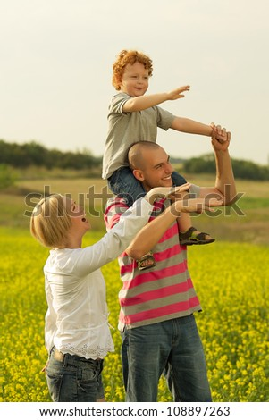 happy family. father holding son in his hands in the field of yellow flowers. outdoor shot - stock photo