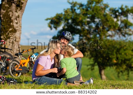Happy family (father, mother and son) on getaway with bikes - they have a break - stock photo