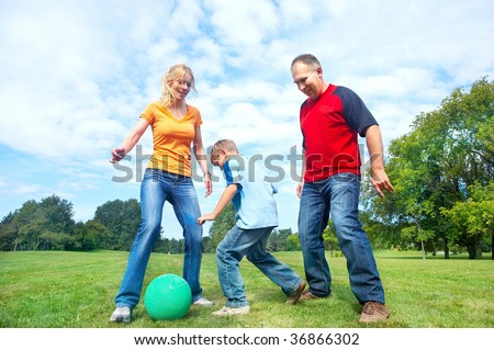 Happy family. Father, mother and sons playing football  in the park - stock photo