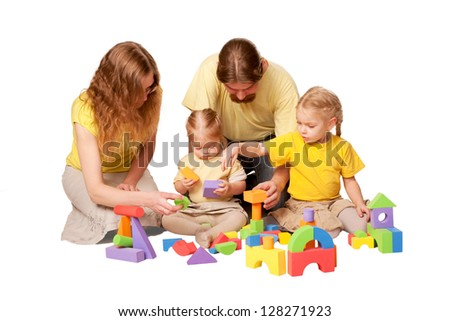 Happy family, father, mother and two children building from toy blocks. Isolated on white background - stock photo