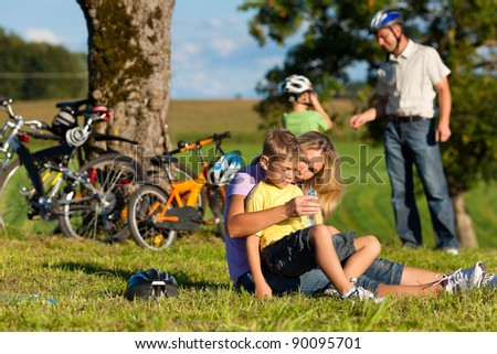 Happy family (father, mother and two sons) on getaway with bikes - they have a break - stock photo
