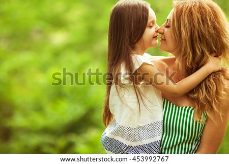 Happy family, friends forever concept. Smiling mother and little daughter walking together in a park. Mom holding baby. Sunny summer day. Close up. Copy-space. Outdoor shot - stock photo