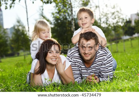 Happy family from four persons lies on a summer lawn - stock photo