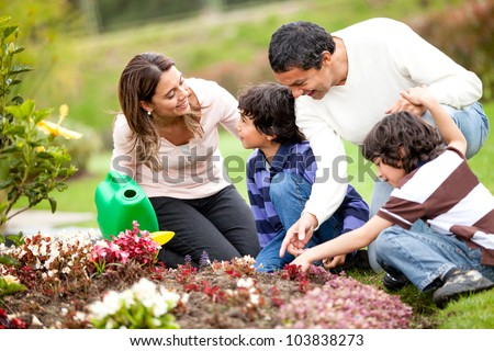 Happy family gardening together and taking care of nature - stock photo