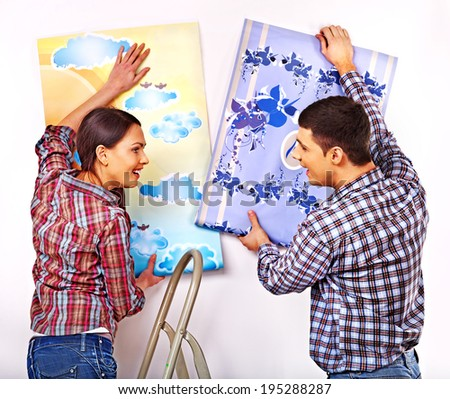 Happy family glues wallpaper at home. - stock photo