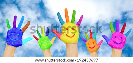 Happy family hands in colorful paints with smiles on background of blue sky with clouds.  - stock photo
