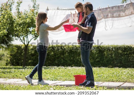 Happy family hanging up laundry - stock photo