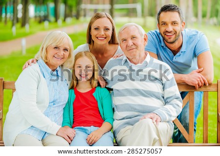 Happy family. Happy family of five people bonding to each other and smiling while sitting outdoors together  - stock photo