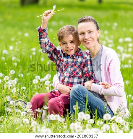 Happy family have fun in the park. focus on mother - stock photo