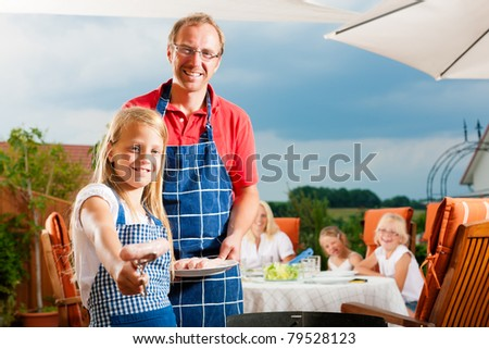 Happy family having a barbecue in summer - stock photo