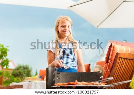 Happy family having a barbecue in summer; the daughter is standing at the grill - stock photo