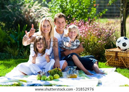 Happy family having a picnic in a park with thumbs up - stock photo