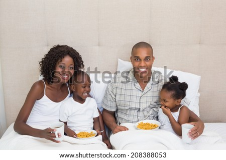 Happy family having breakfast in bed together in the morning at home in the bedroom - stock photo