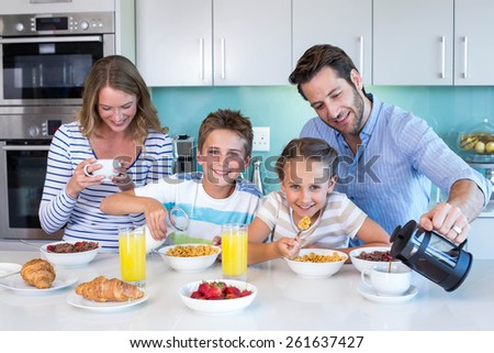 Happy family having breakfast together at home in the kitchen - stock photo