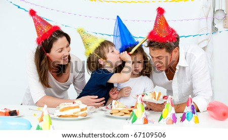Happy family having fn while eating birthday cake in the kitchen - stock photo