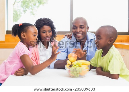 Happy family having fruit together at home in the kitchen - stock photo