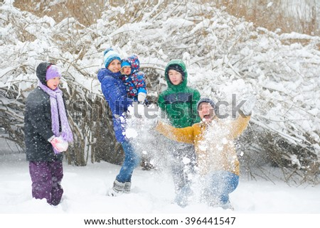 Happy family having fun and playing with snow outdoors in winter nature. Family Christmas holiday walk in a snowy park with children, kids. - stock photo