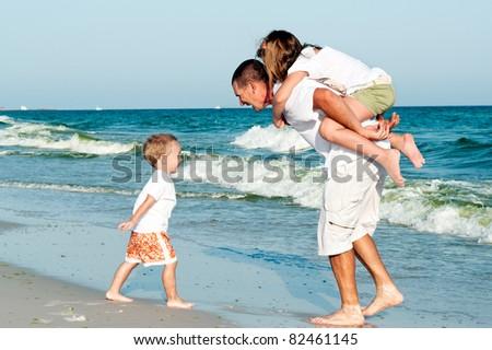 Happy family having fun  at the beach - stock photo