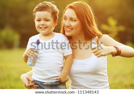 happy family having fun. baby boy with brown curly hair and  his mother with ginger hair showing thumbs up. outdoor shot - stock photo