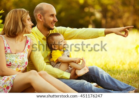 Happy family having fun. Baby boy with his mother and father sitting together in he park. Dad shows something. Outdoor shot - stock photo