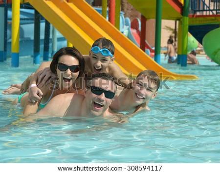 Happy family having fun in a pool - stock photo