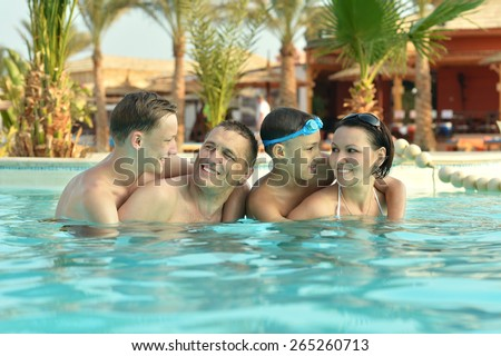 Happy family having fun in pool with thumbs up - stock photo