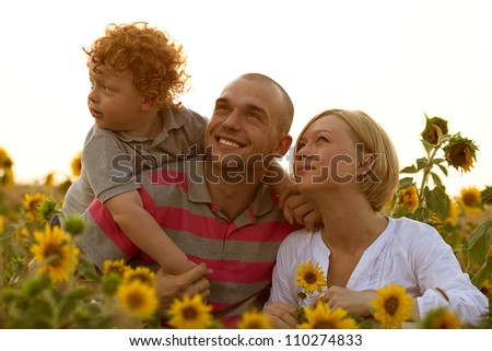 happy family having fun in the field of sunflowers. Father and mother watching something up in the sky. outdoor shot - stock photo