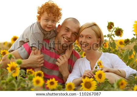 happy family having fun in the field of sunflowers. Father holding his son. Mother holding sunflower. outdoor shot - stock photo