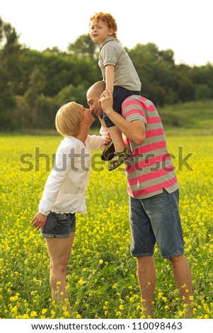 happy family having fun in the field with yellow flowers. mother and father kissing. outdoor shot - stock photo