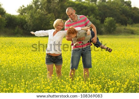 happy family having fun in the field with yellow flowers. Mother doing plane figure. outdoor shot - stock photo
