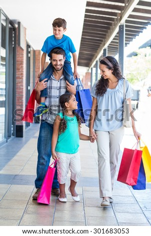 Happy family having fun in the mall on a sunny day - stock photo