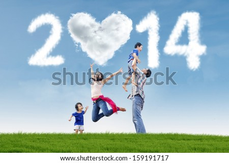 Happy family having fun in the park with heart shaped cloud of new year 2014 - stock photo
