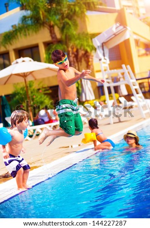 Happy family having fun in the pool, son jumping into the water, relaxed in aquapark, beach resort, summer vacation, travel and tourism concept - stock photo