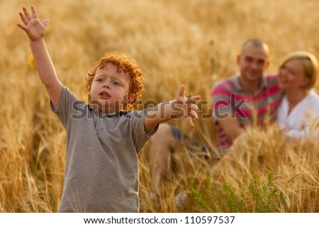 happy family having fun in the wheat field. Father and mother behind their son. Son's hands up. outdoor shot - stock photo