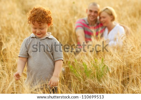 happy family having fun in the wheat field. Father and mother hug each other behind their son. Son whatching wheat. outdoor shot - stock photo