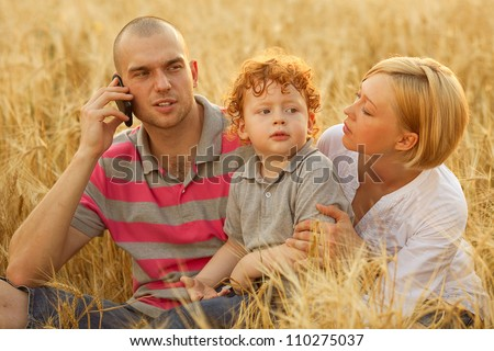 happy family having fun in the wheat field. Father callig.Mother looking at her own son. outdoor shot - stock photo
