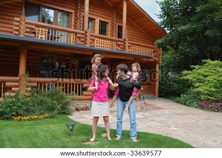 Happy family having fun near theit house - stock photo