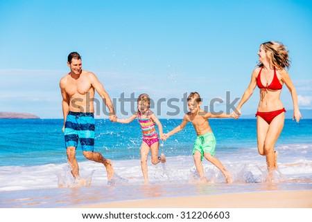 Happy family having fun on beautiful warm sunny beach.  - stock photo