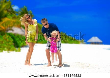 Happy family having fun on tropical beach on Maldives - stock photo