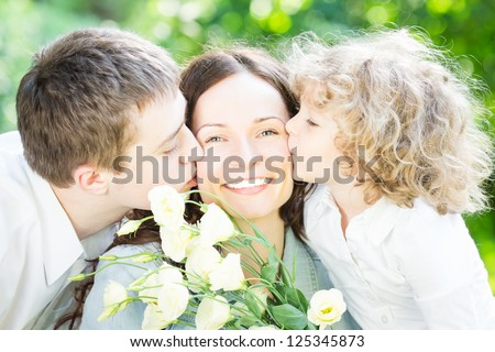Happy family having fun outdoors in spring park against nature green background. Mother`s day concept - stock photo
