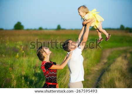 Happy family having fun outdoors in summer meadow. Father playing with child. Family concept. Picnic. Man holding little girl in hands. Laughing, smiling people - stock photo